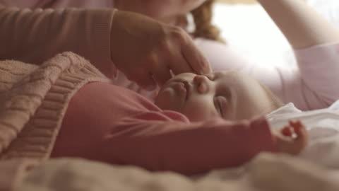 stockvideo's en b-roll-footage met moeder kijken slapende baby op bed - moe