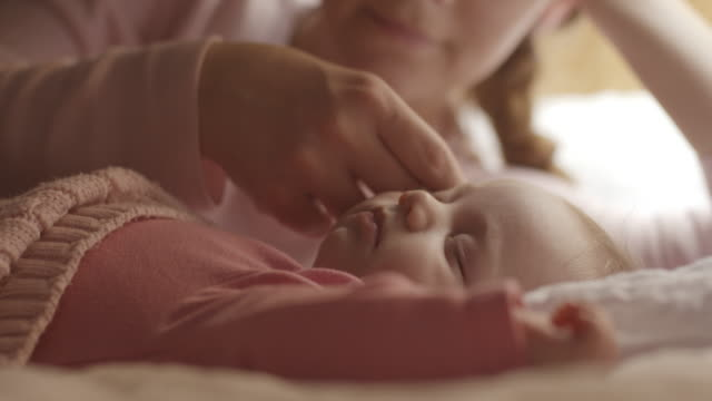 mother watching sleeping baby on bed - bed furniture stock videos and b-roll footage