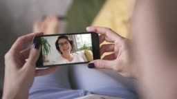 mother waving and blowing kiss to her daughter through smart phone video call