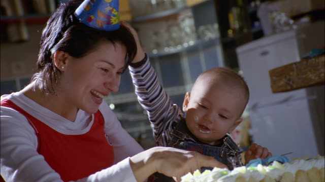 A mother wearing a party hat helps her son stick his fingers in his birthday cake.