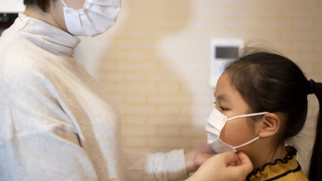 mother wearing medical face mask for daughter - chinese ethnicity stock videos & royalty-free footage