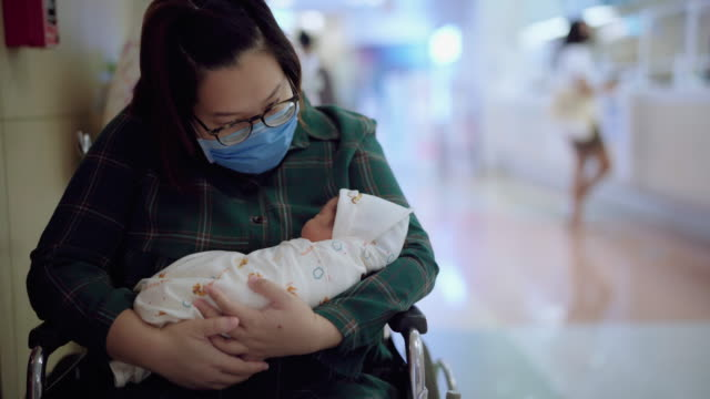 mother wearing prevention virus masks admiring sleeping newborn baby in hospital - admiration stock videos & royalty-free footage