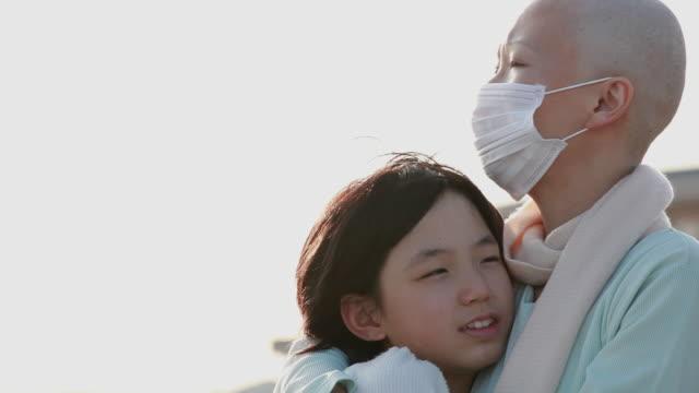 cu mother wearing surgical mask hugging daughter (11-12) standing outdoors / urayasu, chiba, japan - sjukdom bildbanksvideor och videomaterial från bakom kulisserna