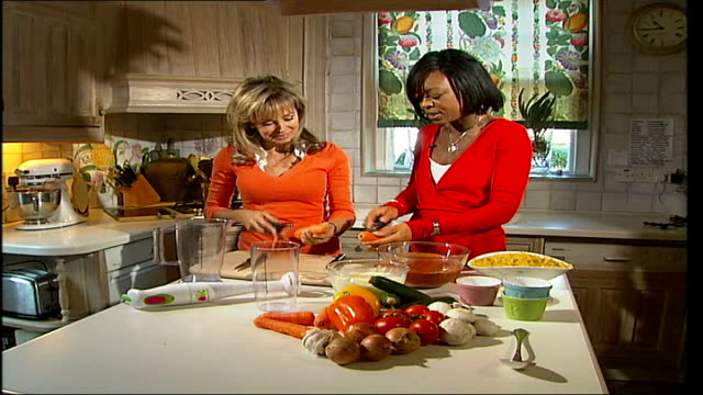 mother who set up children's cookery business annabel karmel interview karmel and reporter scraping carrots karmel interview sot - scraping stock videos and b-roll footage