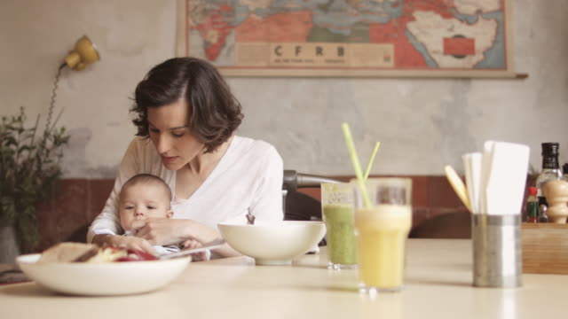 mother wiping baby while having food in restaurant