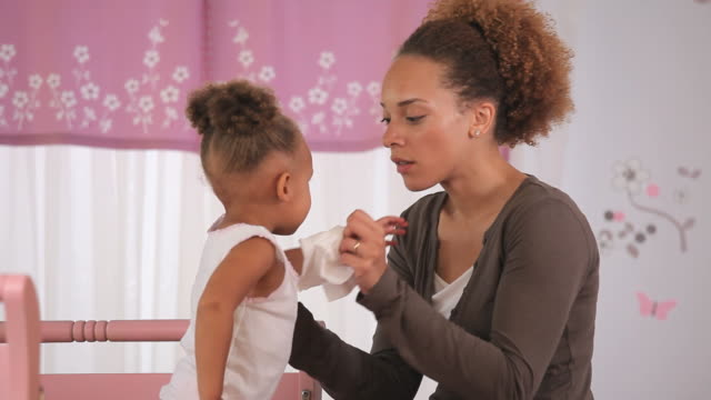 MS PAN Mother wiping daughter's (2-3) nose in nursery / Richmond, Virginia, USA