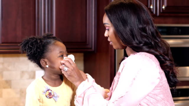 Mother wiping little girl's nose with tissue
