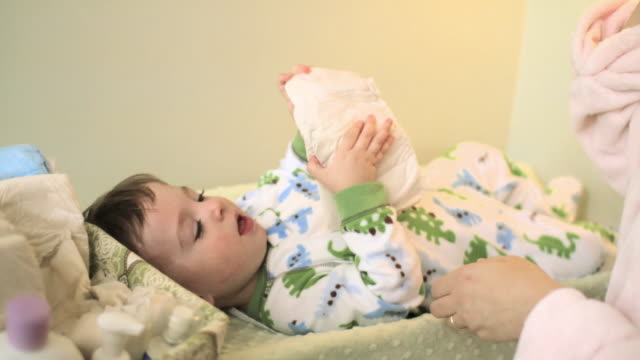 mother with baby boy on changing mat with nappy - babygro stock videos & royalty-free footage