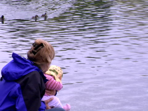 MS, Mother with baby daughter (9-12 months) looking at ducks swimming on water, Lake Wanaka, Wanaka, New Zealand