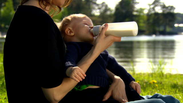 stockvideo's en b-roll-footage met mother with baby, drinking from bottle, teat. - zuigfles