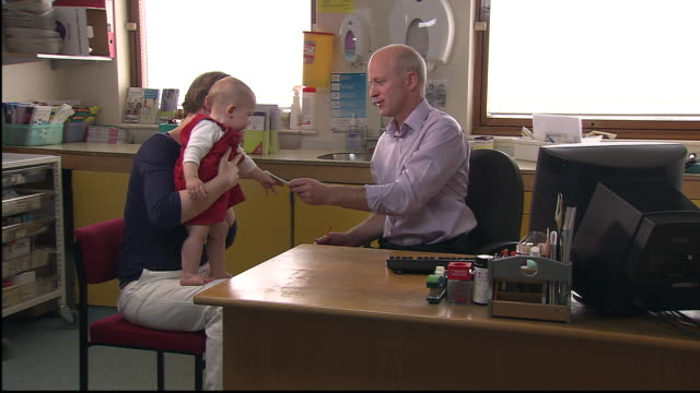 vidéos et rushes de ms, mother with baby girl (12-17 months) talking to doctor in office - 12 17 mois