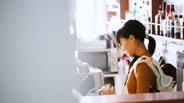 カフェで働く赤ちゃんを持つ母親 - マルチタスク点の映像素材/bロール