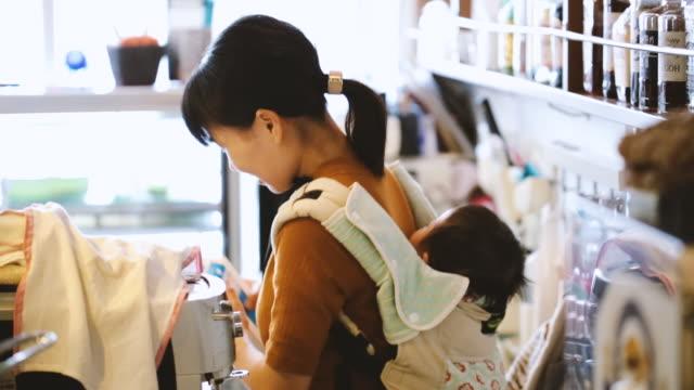 カフェで働く赤ちゃんを持つ母親 - 忙しい点の映像素材/bロール