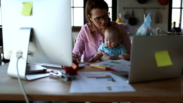 vídeos de stock e filmes b-roll de mother with baby working from home - mãe