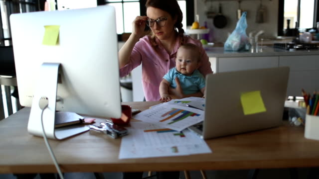 mother with baby working from home - multitasking stock videos & royalty-free footage