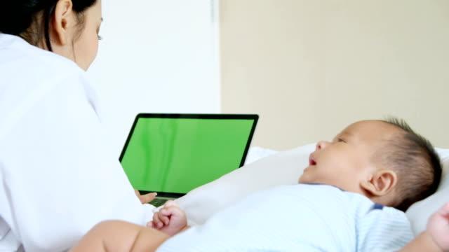 Mutter mit Baby auf dem Laptop, Greenscreen Hintergrund arbeiten.