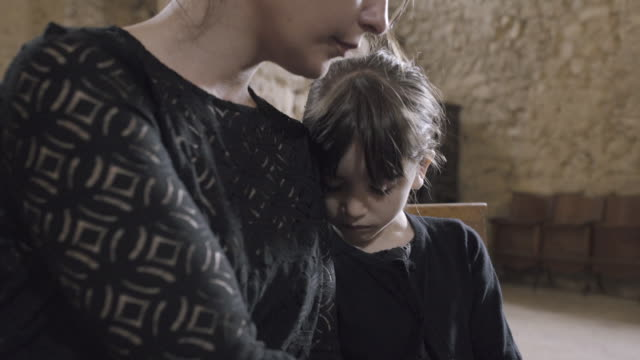 mother with child at a funeral - begräbnis stock-videos und b-roll-filmmaterial