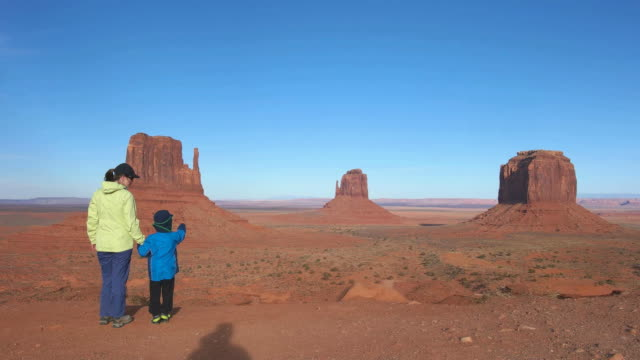 mother with child looking at view in monument valley utah usa - monument valley stock videos & royalty-free footage