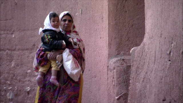 ms mother with child walking down village alley, abyaneh, iran - iran stock-videos und b-roll-filmmaterial
