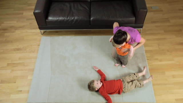ws mother with children playing on carpet / london, uk  - familie mit zwei kindern stock-videos und b-roll-filmmaterial
