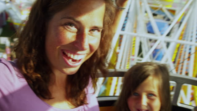 ms pan tu mother with children (4-9) sitting in amusement park ride / rutland, vermont, usa - arts culture and entertainment stock-videos und b-roll-filmmaterial