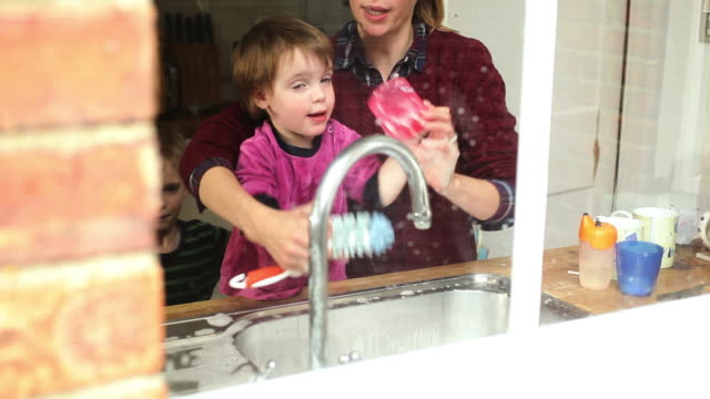 Mother with children standing besides kitchen sink