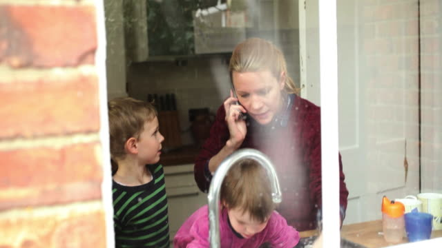 Mother with children standing besides kitchen sink