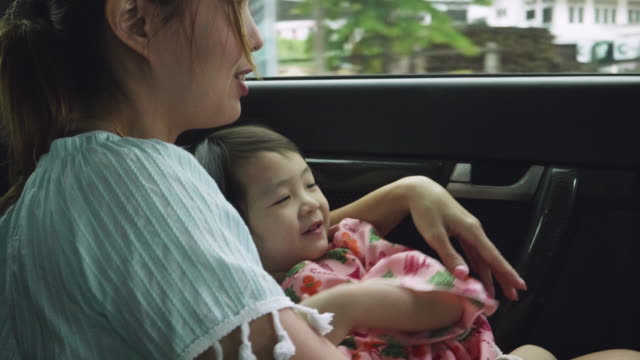 Mother With Children Traveling In The Back Of A Car