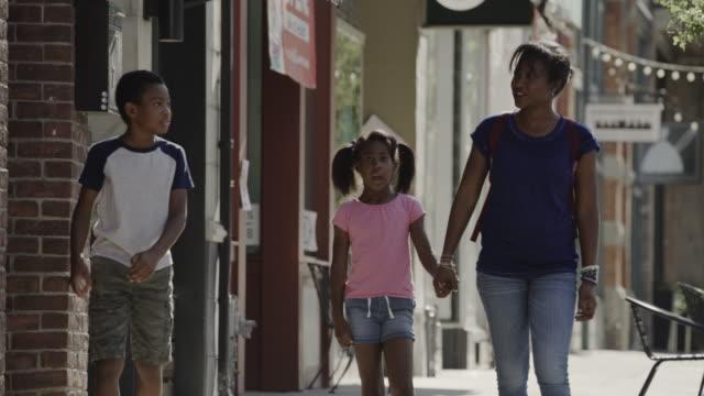 mother with daughter and son walking on city sidewalk / provo, utah, united states - 6 7 år bildbanksvideor och videomaterial från bakom kulisserna