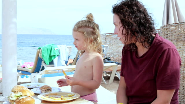 mother with daughter have lunch on the beach of the red sea. - red potato stock videos & royalty-free footage