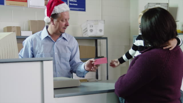 ms tu mother with daughter (4-5) mailing card at post office, postal worker giving candy cane to girl / orem, utah, usa - post office stock videos and b-roll footage