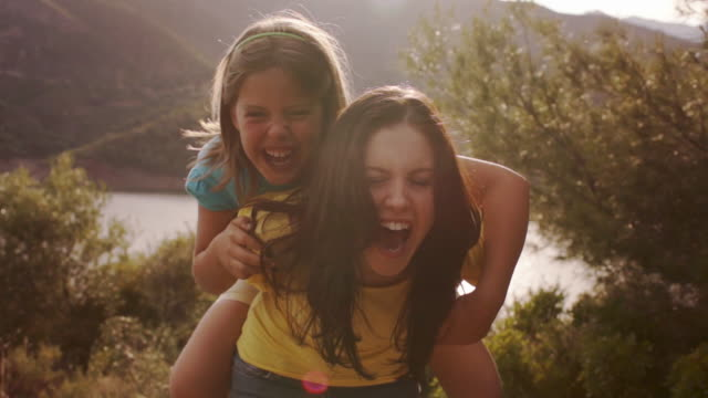 vídeos de stock e filmes b-roll de mother with daughter on back, playing overlooking lake in countryside. - cavalitas