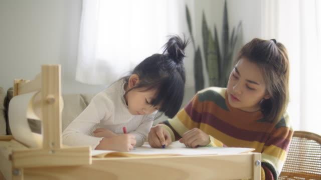 vídeos de stock, filmes e b-roll de mãe com filha estudando em casa - aplanar a curva