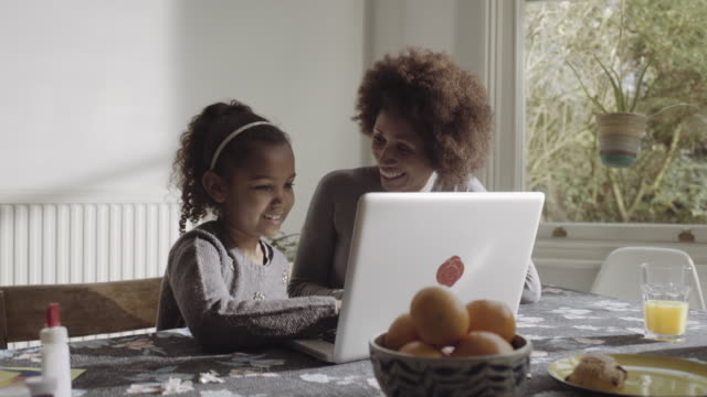 Mother with daughter teaching on laptop in kitchen