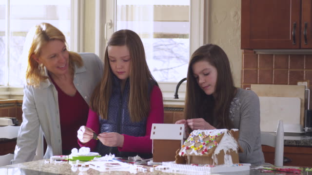 ms mother with daughters decorating gingerbread house / rutland,vermont, usa - 子供2人の家庭点の映像素材/bロール