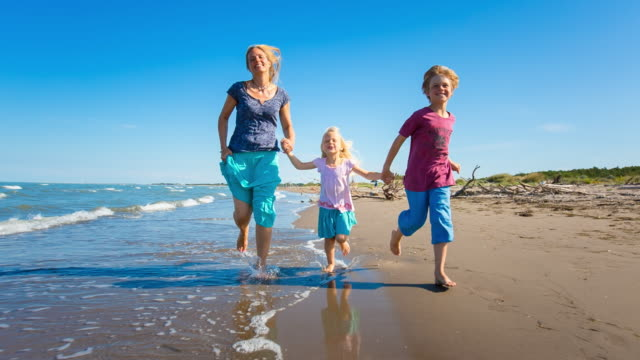 mother with girl and boy running along Adriatic sea beach, steady cam