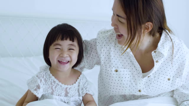 Mother with girl playful on bed