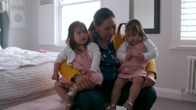 彼女の2人の若い娘を持つ母親は、寝室で自宅で彼女の膝の上に座っています - 依存点の映像素材/bロール