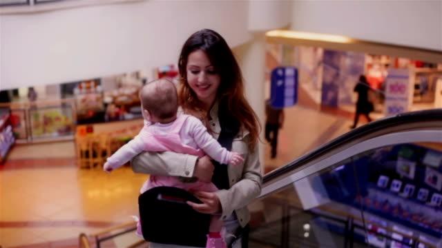 mother with her baby at the escolator in shopping mall - okänt kön bildbanksvideor och videomaterial från bakom kulisserna