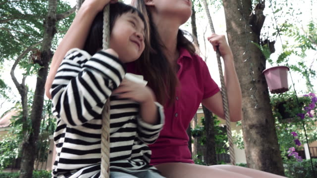 mother with her child having fun on playground swing - swinging stock videos & royalty-free footage