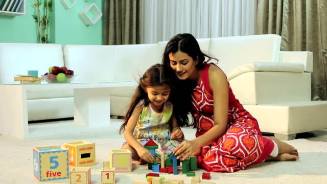 Mother with her daughter arranging building blocks, Delhi, India