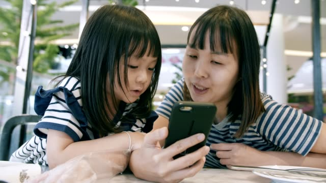 mother with her daughter using a smartphone - family with one child stock videos & royalty-free footage