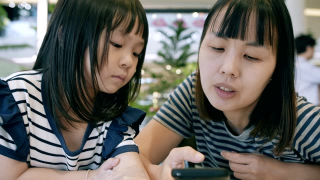 mother with her daughter using a smartphone - baby girls stock videos & royalty-free footage
