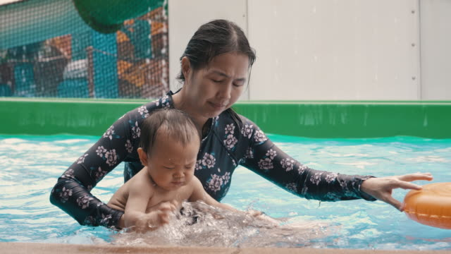 mother with her son having fun at a water park - 6 11 months stock videos & royalty-free footage