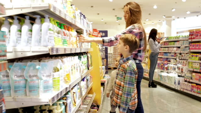 Mother with kids shopping hygiene products, panning shot