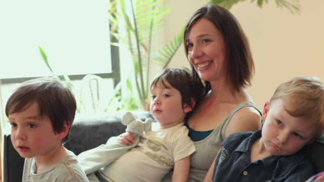 stockvideo's en b-roll-footage met ms mother with kids (2-5) sitting on sofa / brooklyn, new york city, usa - familie met drie kinderen