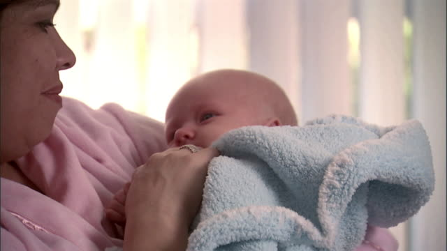 SLO MO, CU, PAN, Mother with newborn baby in hospital room