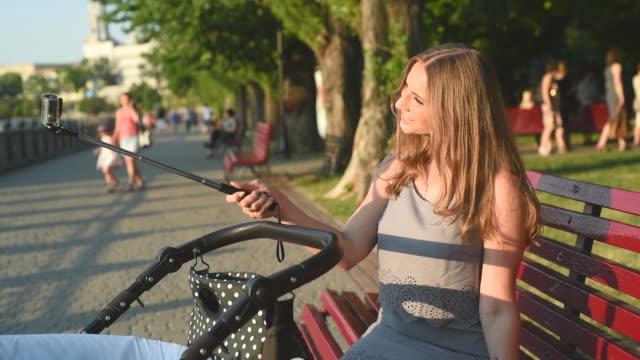 Mutter mit Kinderwagen spazieren im park an einem sonnigen Tag