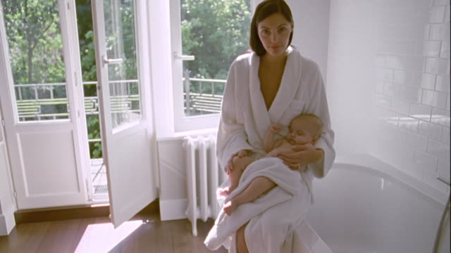 MS, Mother with sleeping baby boy (2-5 months) sitting on edge of bath, Brussels, Belgium