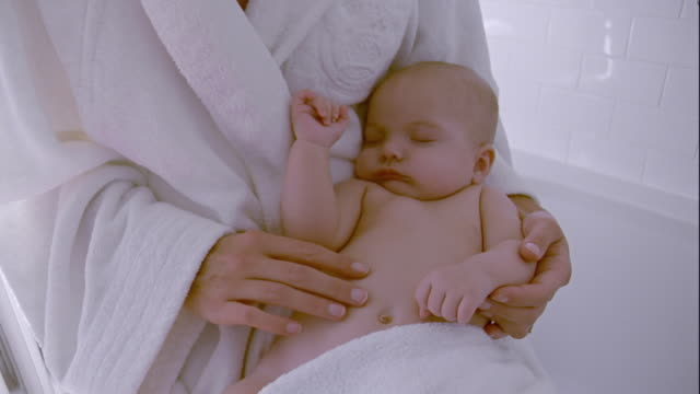 cu, tu, mother with sleeping baby boy (2-5 months) sitting on edge of bath, brussels, belgium - タオル点の映像素材/bロール